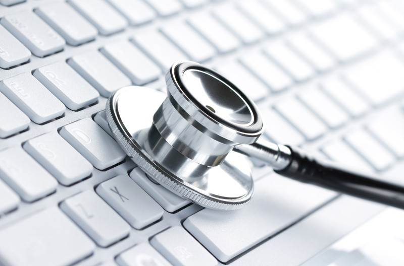 14811361 – silver stethoscope lying down on an laptop