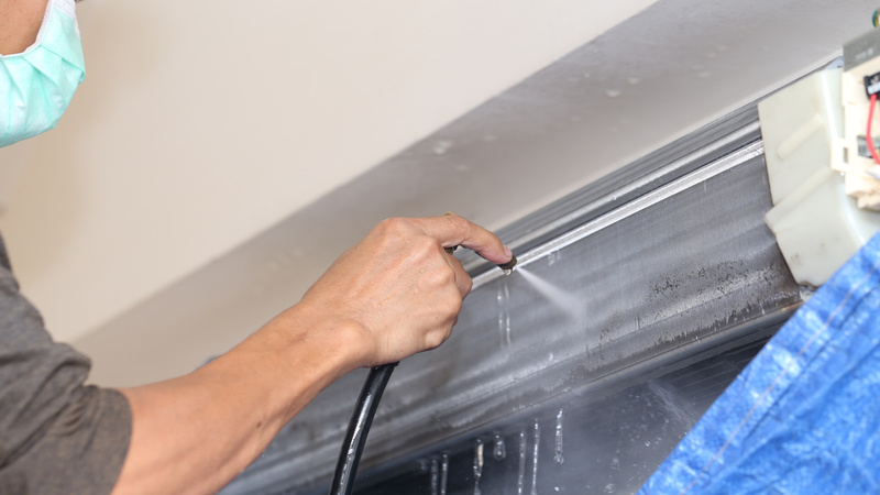 Repairman fixing and cleaning air conditioner unit