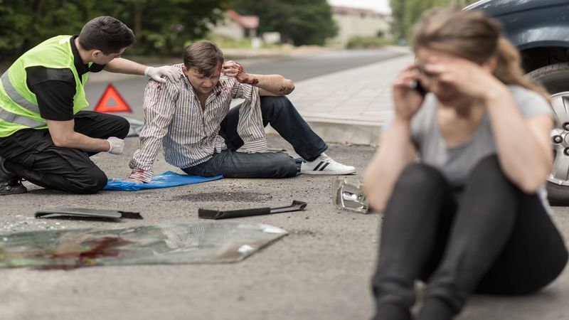 52950544 – people sitting on the road after car crash