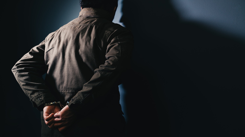 Arrested male criminal with handcuffs facing prison wall