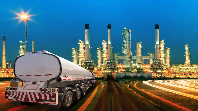 petroleum container truck and beautiful lighting of oil refinery plant in  heav petrochemicaly industry estate use for power ,energy and petroleum industrial topic